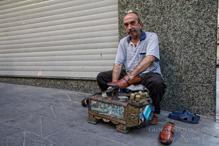 man shining shoes on the corner