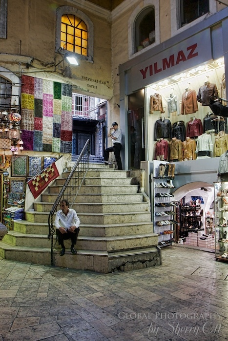 A vendor sits on the stairs