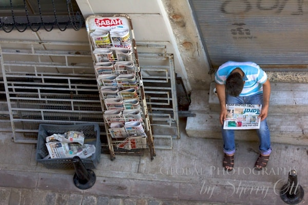 A man reads the newspaper out on the stoop