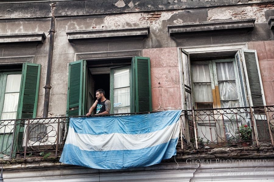 A man looks out his balcony during the Sunday San Telmo market