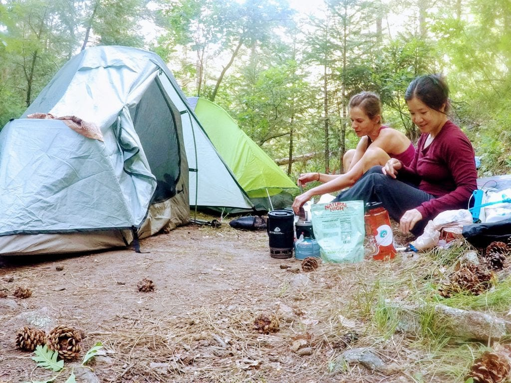 two hikers having dinner while camping