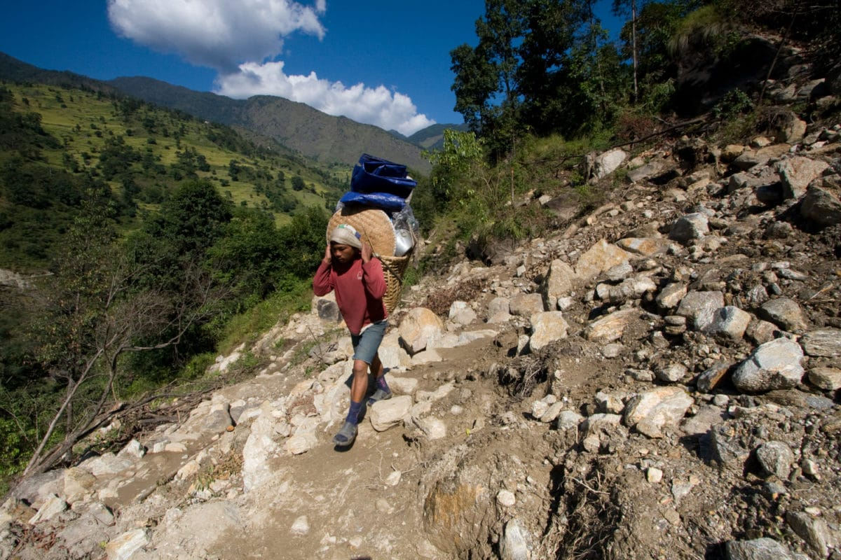 Nepalese porters carry loads with their necks
